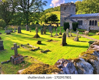 English graveyard with tombstones on green grass with the chapel behind and a rock fence at the front