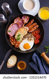 English or Irish breakfast with sausages, bacon, eggs, tomatoes, mushrooms and beans on frying pan. Nutritious and healthy morning meal. View from above, top studio shot