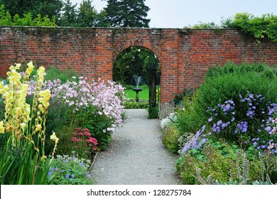 An English Landscape garden with colorful borders of Summer flowers and arch through a wall