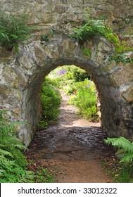 An English Landscape garden  with footpath under a stone bridge