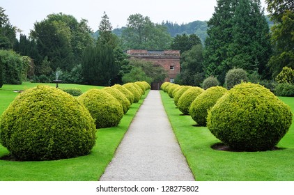 An English Landscape garden with path between ornamental Topiary