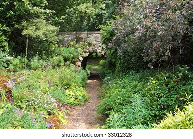 An English Landscape garden in Summer with footpath leading to a bridge