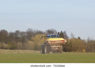 an english landscape with a tractor spreading fertilizer on a field under a blue sky