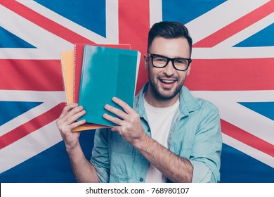 English language learning concept-portrait of cheerful attractive man with bristle showing colorful copy books standing over English flag background