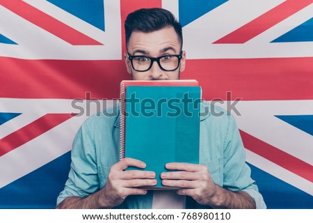 5668a905df6d English language learning concept-portrait of excited man holding colorful  copy books in hands closing