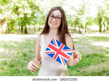 English Language Learning, smiling pretty woman student with British national flag outdoor, education concept