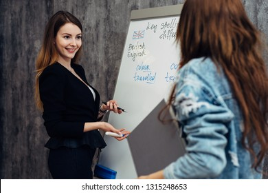 English language school. Two female students talking in classroom.