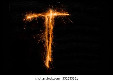 3d10a0d964 The English letter T made of sparklers on black background