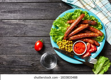 English meal: pork sausages chipolata roasted and served on a blue plate with tomato ketchup, tomatoes, green lettuce, and peas on a rustic wooden background, top view, close-up