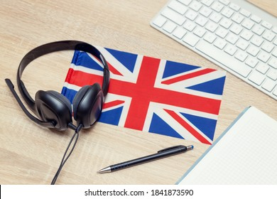 English online. Student desk with headphones, keyboard, glasses, notepad, pen. Listening and taking notes of audio lessons. Hosting a webinar. Learning language.