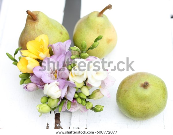 English pear and freesia,  on a wooden painted vintage crate, spring wedding table decoration , shallow depth of field, shot from above with underexposure