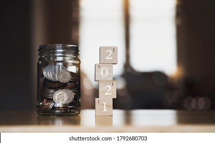 English pound string coin and pennies nickels in jar with 2021 on wooden stack with blurry background,Financial planing for 2021 New Year resolution for saving money for future in business or life