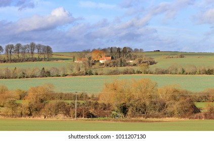 An English Rural Landscape in the Chiltern Hills in Bucks in Winter sunshine with Farmhouse on a hill