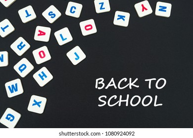 english school concept, text back to school, colored square english letters scattered on blackboard