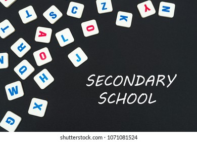 english school concept, text secondary school, colored square english letters scattered on blackboard