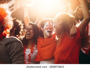 English soccer fans watching the match from the stadium and celebrating after their team scoring a goal. Spectator at stadium cheering when their national team scores a goal.