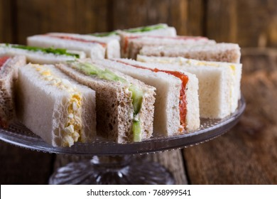 English tea sandwiches on cake over rustic wooden background