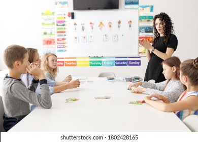 English teacher with children in the classroom. Surprised teacher, English courses