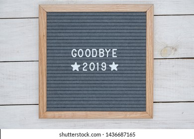 English text goodbye 2019 and two stars on a felt Board in a wooden frame. white letters on a gray background. letterboard on white wooden background