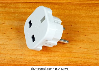 English three pin plug to European style adapter against a wooden background.