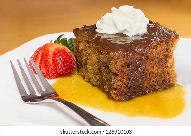 English toffee pudding topped with vanilla whipped cream on white plate