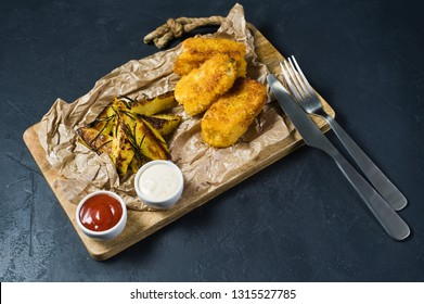 English traditional fish and chips on a wooden chopping Board. Dark background, side view