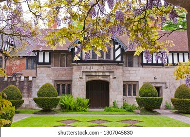 English Tudor Manor House through a Wisteria draped archway