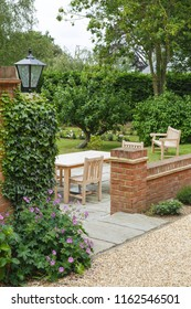 English UK garden in summer with patio and garden furniture