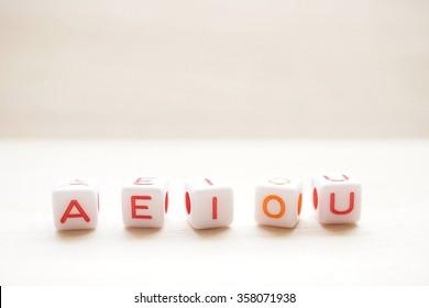 English vowel wooden blocks on wooden background