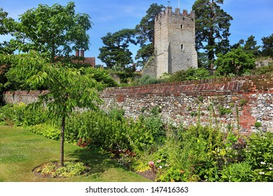 An English walled garden against a blue summer sky with Church in the background