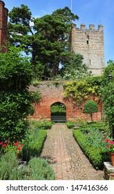 An English walled garden against a blue summer sky with Church steeple