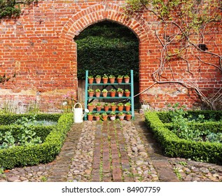 An english Walled garden with Box Hedging and Flowerpot stand
