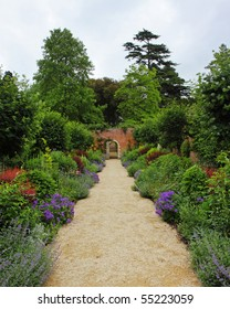 An English Walled Garden in early Summer with path leading to an arched gate
