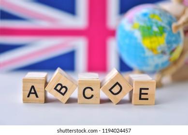 English wooden alphabet block with world globe and England flag symbol background