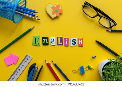 English word of carved letters on yellow background with office or school supplies,English language learning concept