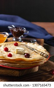 English-style pancakes with berries, traditional for Shrove Tuesday. Traditional classic thin golden flapjack on the plate and napkin on the wooden background.