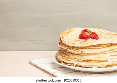 English-style pancakes with strawberry, traditional for Shrove Tuesday. Traditional classic thin golden flapjack on the plate and napkin