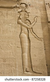 Engraved figure of ancient Egyptian goddess Isis on the wall of the Philae temple in Egypt. The face has been destroyed by Egypt's subsequent conquerors.