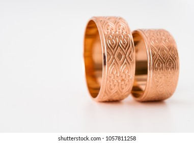 engraved gold wedding rings on white background, close-up