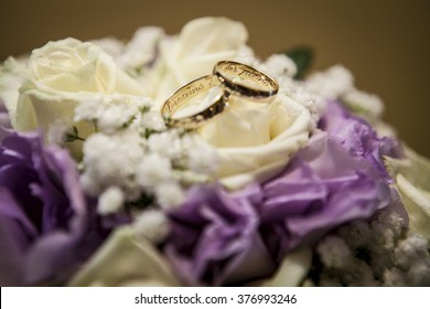 Engraved gold wedding rings with text on flowers