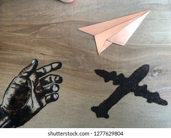 Engraved wood painted and brushed reprinting hope dreams aspirations flying away coming true with plane shadow, paper airplane, pointing hand. Let your dreams fly into reality.