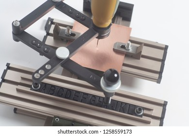 Engraving device pantograph with CNC engraver with letterpress alphabet on a white background