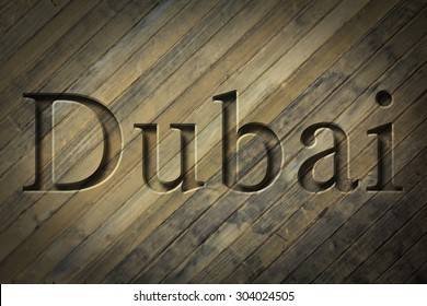 Engraving spelling the city Dubai on textured old surface