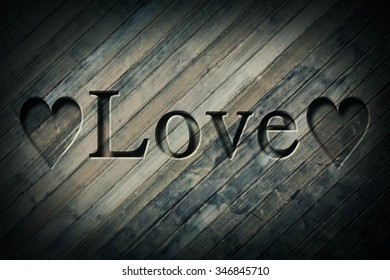 Engraving spelling the word Love on textured old surface