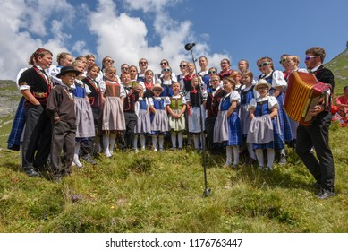 Engstlenalp, Switzerland - 4 August 2018: People wearing traditional clothes yodeling at Engstlenalp on the Swiss alps