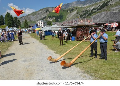 Engstlenalp, Switzerland - 4 August 2018: People playing the alphorn and flag bearers at Engstlenalp on the Swiss alps