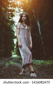 An enigmatic beautiful girl walking in a forest. Beauty, fashion.