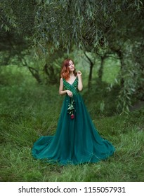 enigmatic girl in the clearing of grass is holding a rose in hands