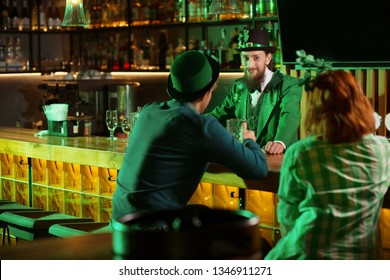 Enigmatic looks. Dark-haired bearded young man in a leprechaun hat looking enigmatic while standing at the bar counter