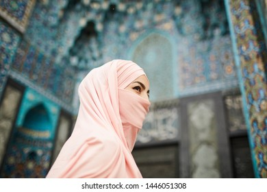 Enigmatic Muslim lady with covered face going to beautiful mosque with ornamental design and looking away